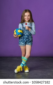 Little girl in jeans overalls,sneakers,keeps ball for playing volleyball,eats candy. Fashion beautiful child model,perfect cute smile for advertising sport,lifestyle style.Purple background in studio.