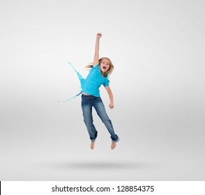 Little girl jumping with clothes turning to paint splashes on grey background
