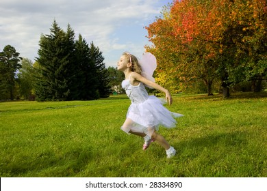 Little girl jumping happily on the grass