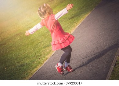 Little girl jumping with joy on a path in a park in spring