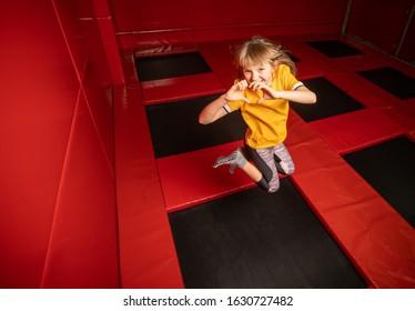 Little girl jumping on trampoline in fly park