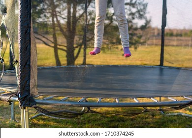 Little girl jumping on the trampoline in the back yard. Teenager bouncing on the trampoline