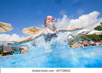 little girl jumping to swimming pool at resort
