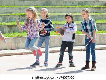 Little girl jumping while jump rope game with friends outdoor