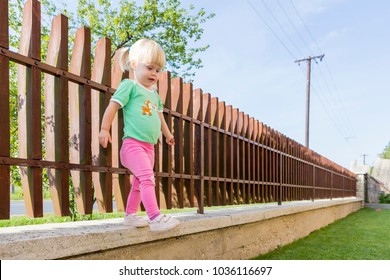 Little girl jumps from the edge of the fence.