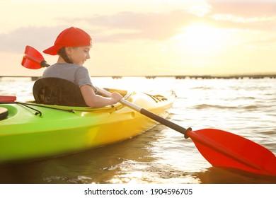 Little girl kayaking on river, back view. Summer camp activity