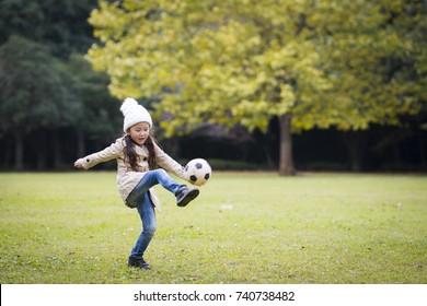 Little girl kicking a soccer ball