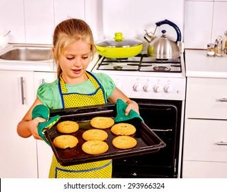 Little girl kid   baking hot cookies in oven.