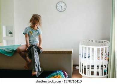 Little girl kid getting dressed by herself, going to kindergarten in the morning. Clock on the wall in bedroom