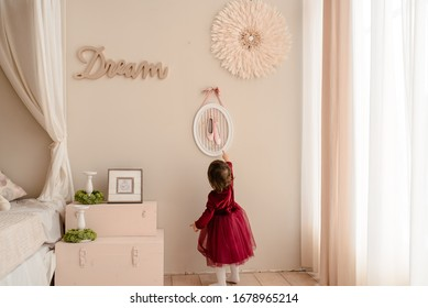 Little girl kid in vintage interior that standing on the suitcase and dreaming to become a ballerina
