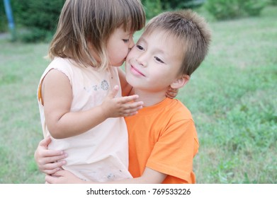 little girl kissing boy, happy siblings childhood