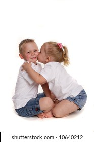 Little girl kissing her brother on the cheek