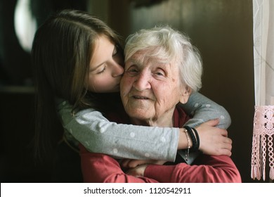 Little girl kissing her grandmother.