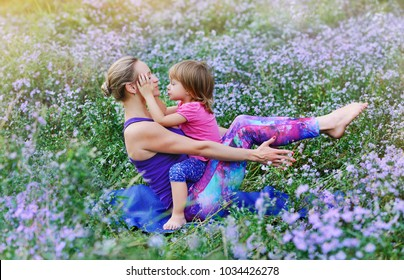 Little girl kissing her mother while she is practicing yoga in a flower meadow