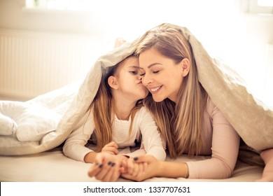 Little girl kissing her mother under blanket.