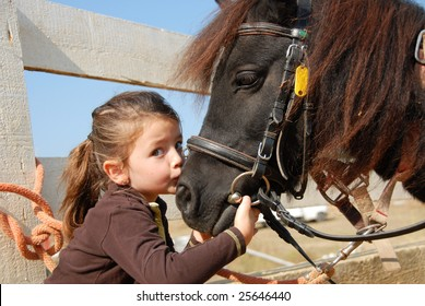 little girl kissing and her purebred shetland pony