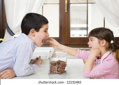 little girl in the kitchen giving a cookie to her brother