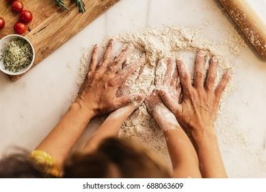 Kleines Mädchen, das Mehl mit seiner Mutter knetet. Kinderkochkonzept.