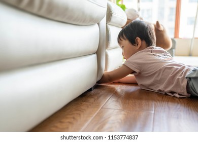 A little girl kneels on the floor and looks for something under the sofa