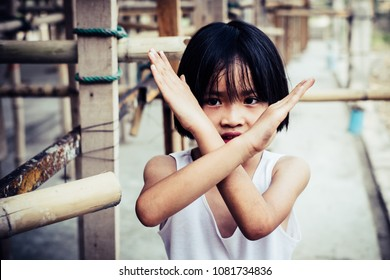 Little girl labor making X shape for Extreme with his hands. World Day Against Child Labour concept.