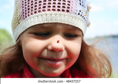 Little girl with ladybug on her nose