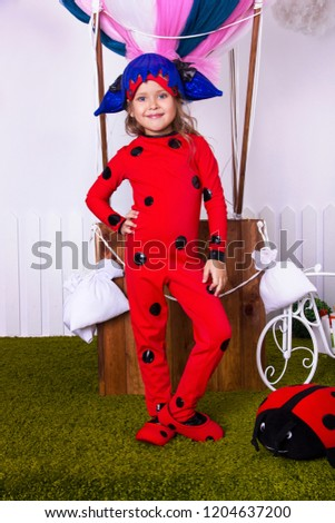33af3f339 little girl in ladybug overalls. kid halloween costume. young girl  superhero in white room