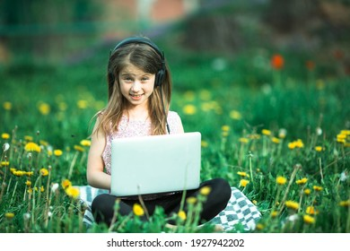 Little girl with laptop lying on outdoor at summer.