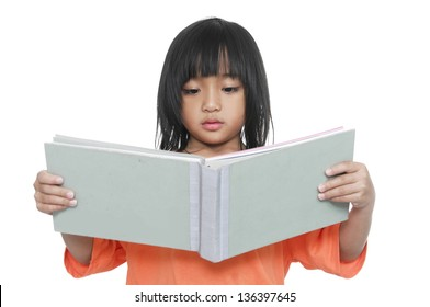 Little girl with large book reading book. Shot in studio over white.