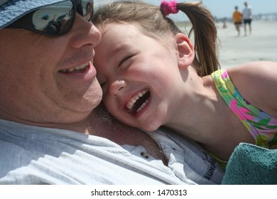 little girl laughing with dad at beach