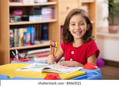 kleines Mädchen, das lacht und ihre bunten Stifte auf ihrem Spieltisch zeigt
