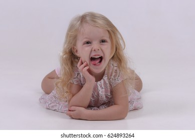 Little girl laughing in the studio laying on the floor