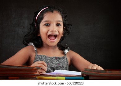A little girl laughs as does her homework in the study room