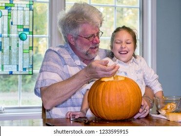 a little girl laughs as grandpa teases her with the slimy insides of a jack o lantern that they are carving for Halloween