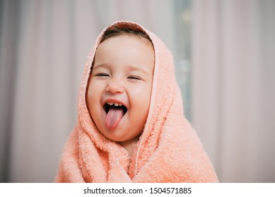 the little girl laughs and shows her tongue sitting in a towel after the bath bought and steamed very cute
