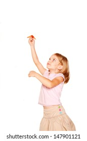 Little girl launching up a hand made paper plane  Isolated on white background.
