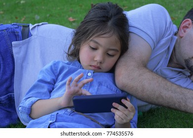 little girl laying on daddy's tummy while watching on smart phone with blurry green park background, filtered tones