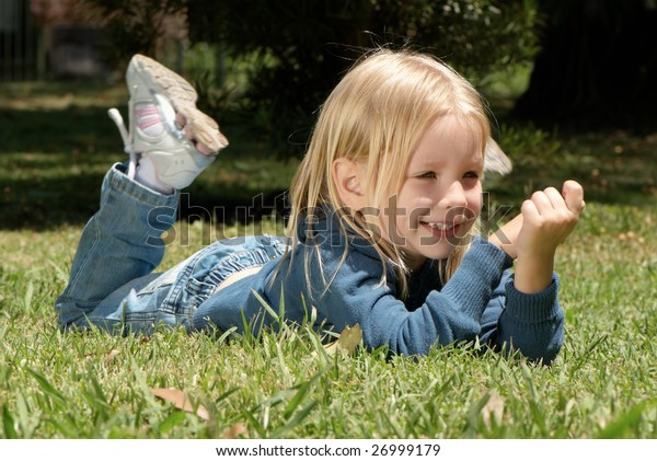 The little girl laying on a grass in park