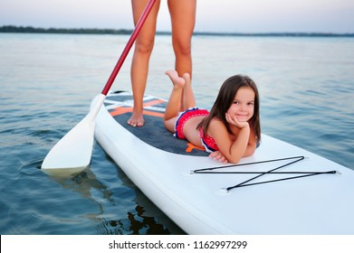 Little girl laying on the sup board white mother is paddling