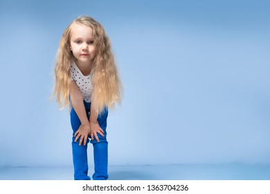 The little girl leaned forward and looked into the camera with long blond hair. On a blue background in the studio.