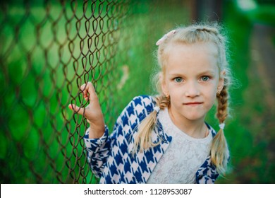 Little girl leaning on fence in park smiling while looking at camera lens