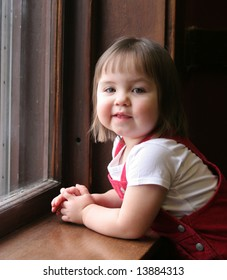 Little girl leaning on a window sill and looking cute