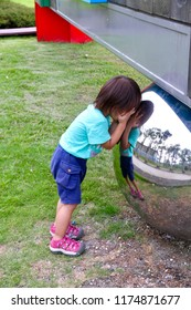 The little girl leans against the stainless ball, counts down and play the game hide and seek.