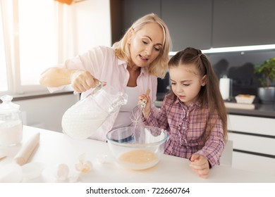 Little girl learn how to cook a home made biscuit. Grandmother helps her pouring milk into a glass bowl with whipped eggs