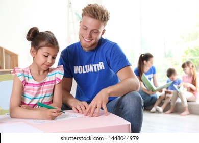 Little girl learning alphabet with volunteer at table indoors