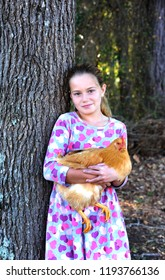 Little girl is learning to care about animals early.  She is holding her pet chicken and leaning against a tree outdoors.