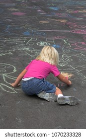 Little girl learning to draw on concrete at local park celebration
