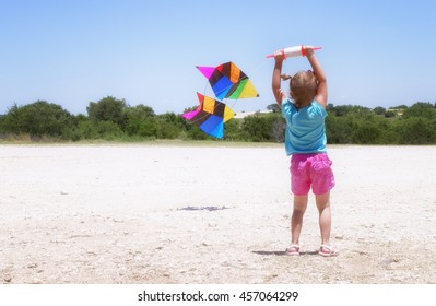 A Little girl learning to fly a kite facing away from the camera