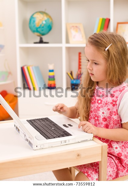 Little girl learning to handle a laptop computer in her room