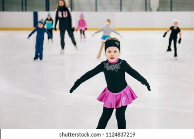 Little girl learning to ice skate. Figure skating school. Young figure skater practicing at indoor skating rink.