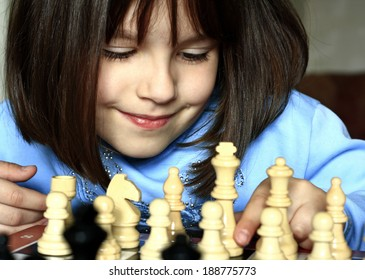 Little girl learning to play chess in the room.